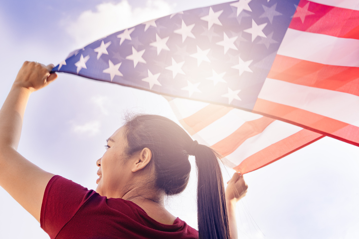 woman holding United States of America flag on sunny sky