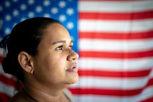 Portrait of woman with American flag on background