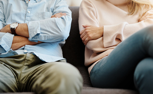 Cropped shot of a divorced couple having a disagreement. Their arms are crossed and they are sitting next to each other.
